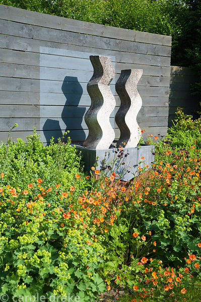 Cast concrete sculpture by Helen Sinclair in the flower garden surrounded by orange and purple geums and aquilegias. Tony Rid...