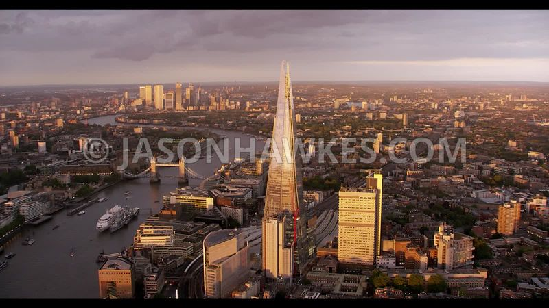 Sunset aerial footage of the Shard, River Thames, Tower Bridge, London with Canary Wharf in far background.