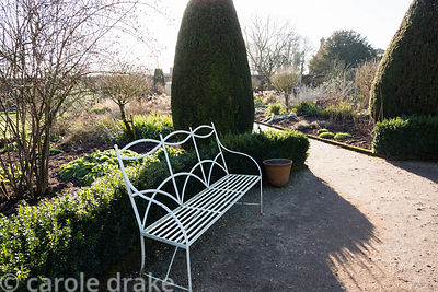 Winter sun casts long shadows around a bench backed by a low box hedge and tall clipped yews in the Rose Garden at Mottisfont...