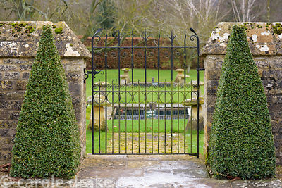 A pair of box pyramids frame a gate into the outer part of the garden at Bourton House in the Cotswolds in January