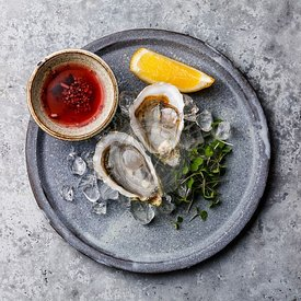 Fresh open Mediterranean Oysters on ice and Mignonette sauce on gray background