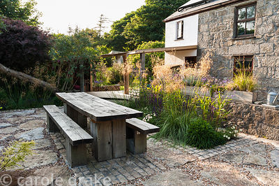 Chunky oak table and benches on a sunny terrace beside the house, with Stipa gigantea, Verbena bonariensis, V. hastata and sa...