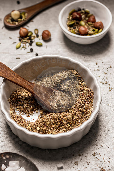 Blended roasted spices, seeds and nuts in bowls on gray background