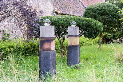 Columns of wood topped by glass spheres in long grass at Broadwoodside, Gifford, East Lothian in September