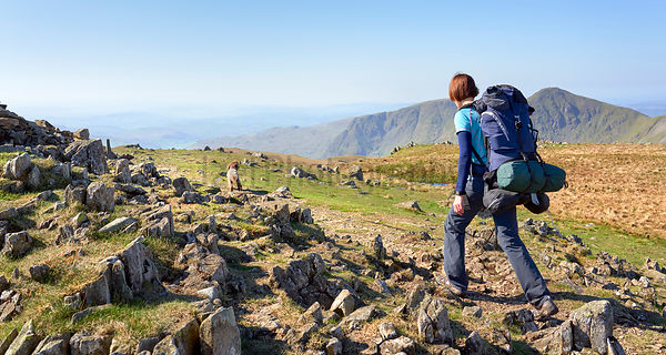 A hiker and their dog backpacking, walking in the mountains in the Lake District below Mardale Ill Bell with Yoke and Ill Bel...