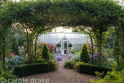Central brick path in the walled garden passes beneath a central rose arch clothed with Rosa banksiae, and is edged with aste...