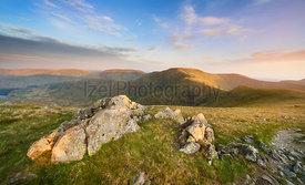 The warm evening glow as sunset approaches over the summit of High Street with Mardale Ill Bell and Harter Fell to the left a...