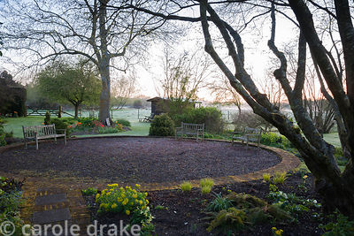 Circular gravel area surrounded by trees, shade planting and seats, with views out across surrounding fields beyond. Terstan,...