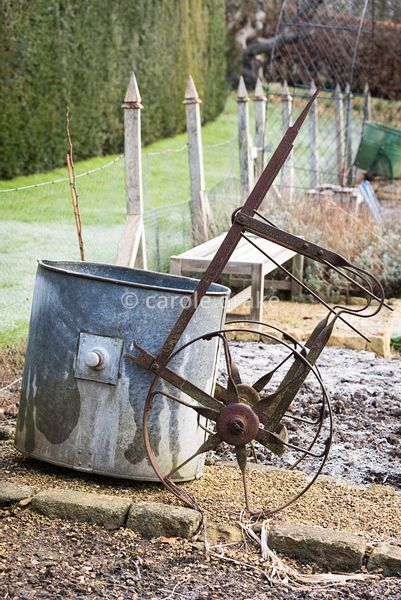Vintage wheeled water container in the formal vegetable garden at the Old Rectory, Netherbury in January