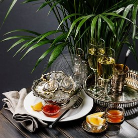 Fresh Oysters on ice in silver bowl and Champagne on black wooden table