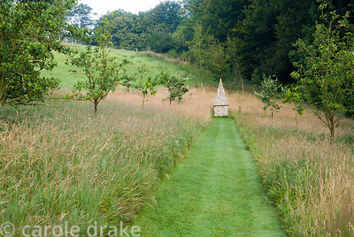 Simple grass path mown through the meadow planted with fruit trees to focal point of flint built obelisk. Corscombe House, Co...