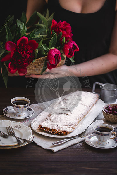 Woman holding flowers next to  sour cherries strudel dusted with powdered sugar