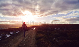 A hiker walking along with their dog on a dirt trail over open moorland at sunset at Edmunbyers in County Durham.