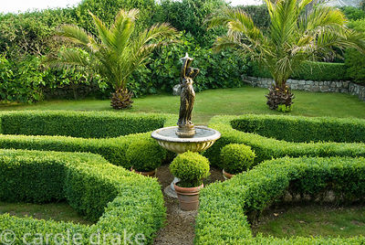 Formal box parterre with central water feature surrounded by box spheres, with date palms and fig hedge beyond. Ednovean Farm...