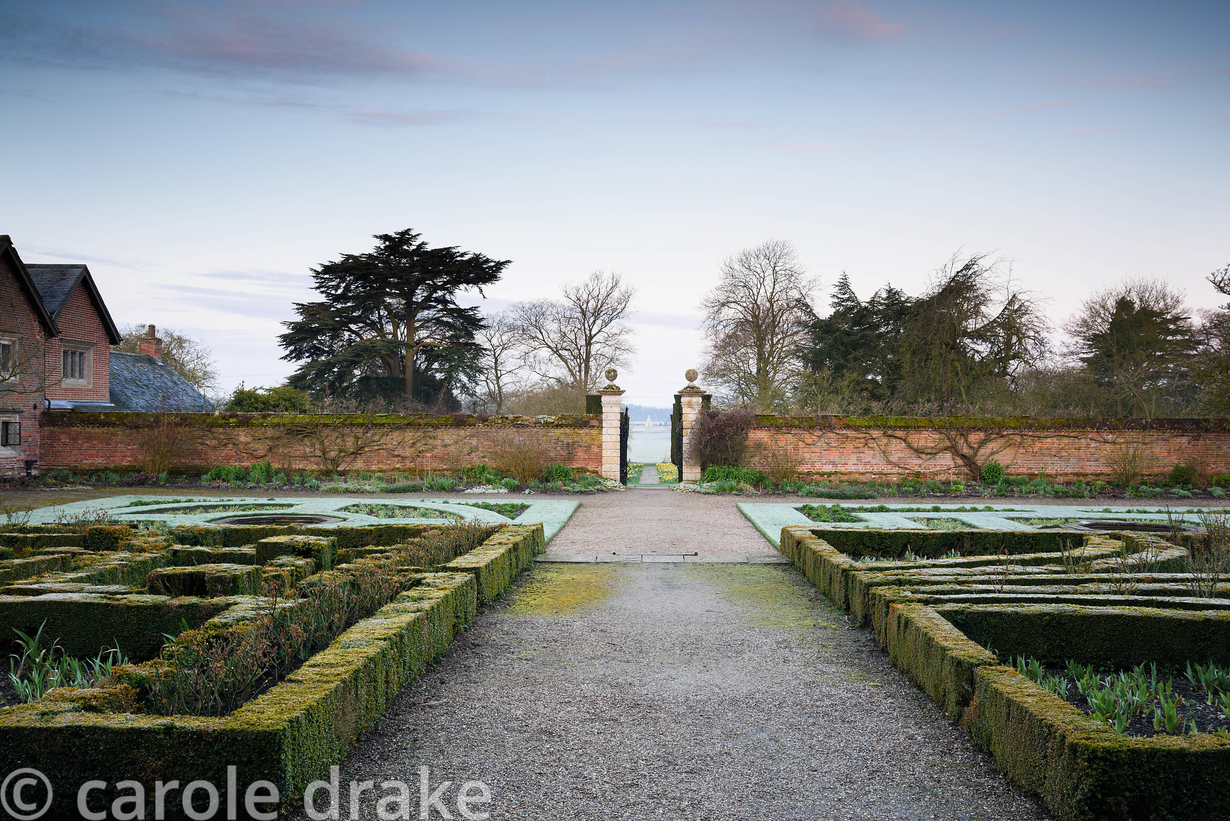 The West Garden on a frosty March morning at Doddington Hall, Lincolnshire with a box parterre and a view out to a pyramid in...