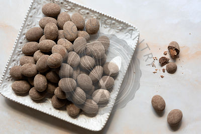 Chai chocolate almonds on a small serving dish.