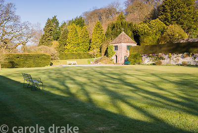 Shadows cast by early morning sun are cast across grass leading toward the swimming pool and summerhouse. Milton Lodge, Wells...