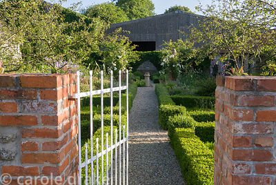 Gate into former farmyard garden defined with low box hedging and planted with Malus 'Red Sentinel'. Private garden, Dorset, ...