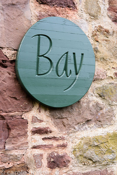 Wooden roundel carved with the word 'Bay' mounted on a wall near others reading, rose, willow and herb at Broadwoodside, Giff...