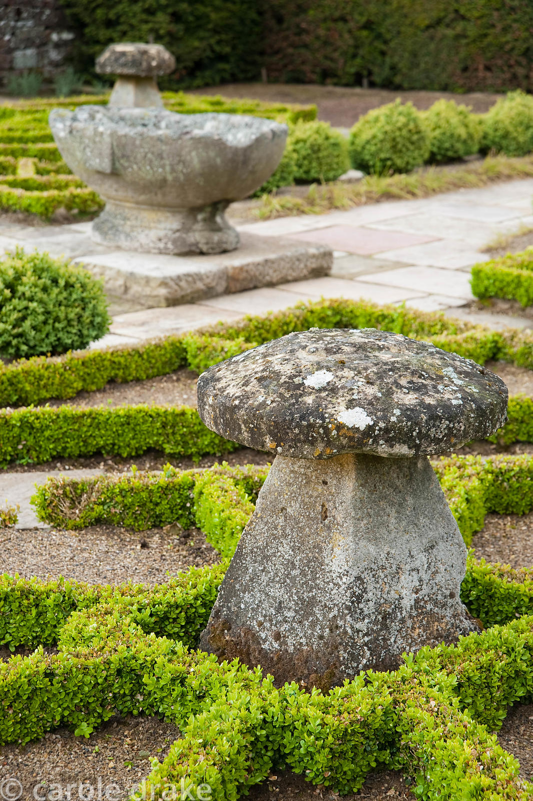 The Fancy Garden includes staddle stones surrounded by clipped box in a pattern based on a Tudor rose pattern. Herterton Hous...