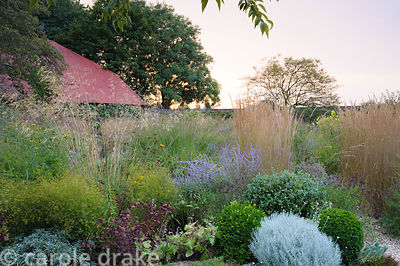 Central circular bed is a mass of graceful grasses and herbaceous perennials including Stipa gigantea, Calamagrostis x acutif...