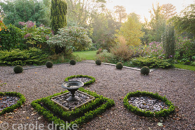 Replanted topiary garden at the front of the house features yew balls and a knot garden of Ilex crenata framed by borders pla...