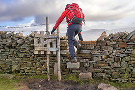 A hiker crossing a stile descending from the summit of Ingleboro