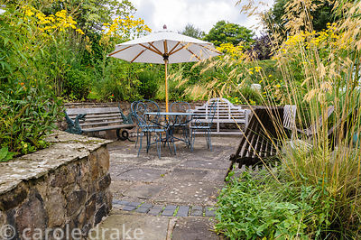 Sunken, paved seating area surrounded by Rudbeckia laciniata and grasses including Stipa gigantea.
