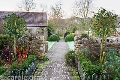 The central path leading across the front garden is framed by standard hollies, clipped box and euphorbias with the bright or...