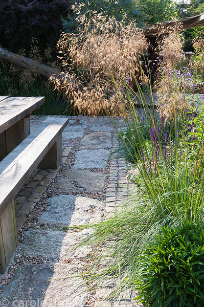 Stipa gigantea with Verbena bonariensis and salvias in a bed on the terrace beside chunky oak table and bench. The 'Garten' G...