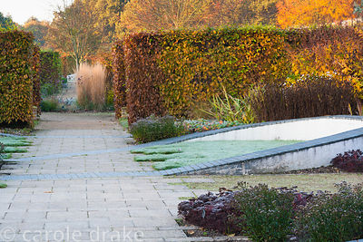 Walled garden designed by Brita von Schoenaich features hornbeam hedges and a ribbon of undulating inlaid grey blocks intersp...