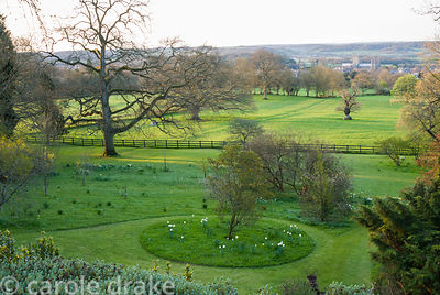 View from the house across naturalistic areas of the garden studded with spring flowers, across surrounding countryside to We...