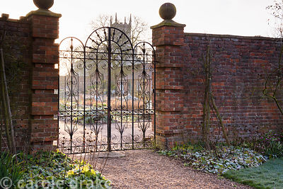 Decorative ironwork gates leading out of the formal garden into the kitchen garden at Doddington Hall, Lincolnshire in March