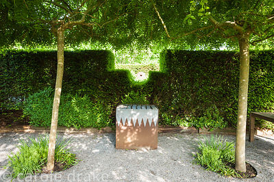 Gravelled courtyard area with four weeping ash, Fraxinus excelsior 'Pendula', framing a steel and lead container filled with ...