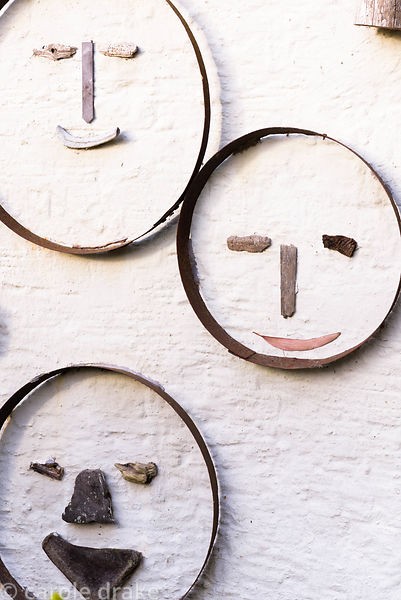 Wall decorated with faces made using the empty frames of vintage sieves with various pieces of wood, shells and other materia...