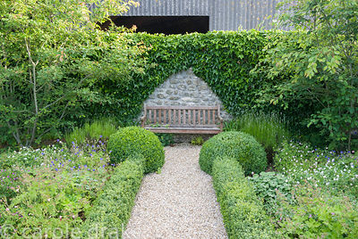 Bench at the end of central axis of courtyard garden laid out with low box hedging infilled with many varieties of hardy gera...