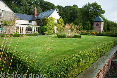 Box hedge surrounds lawn with grasses Stipa gigantea and Stipa tenuissima at its centre and brick build dovecote beyond. Rhod...