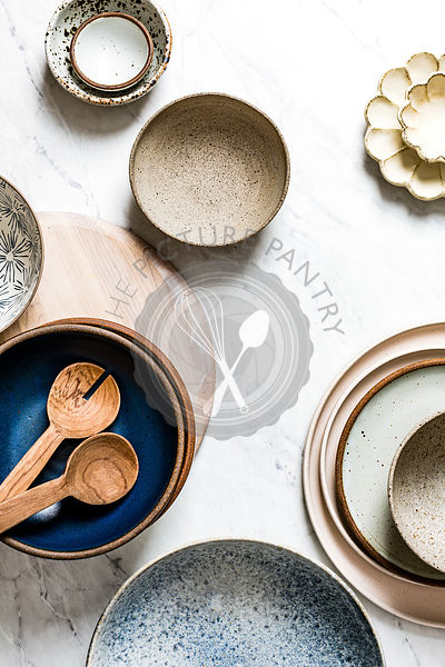 Ceramic bowls and plates on a marble work surface in a kitchen