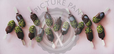 Flat-lay of chocolate glazed ice cream pops with pistachio icing