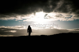 The sun disappearing behind a cloud revealing blue sky and creating a silhouette of a hiking walking off into the distance.