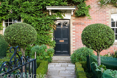 Victorian brick frontage on C18 house, with black door framed by standard pittosporums and formal beds edged with low box hed...
