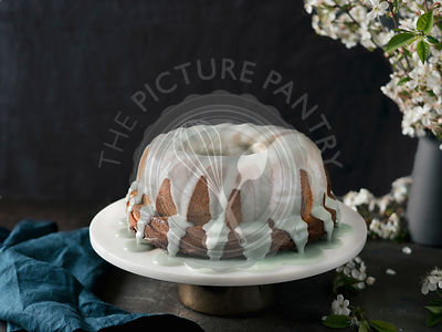 Bundt cake with green matcha glaze on dark table