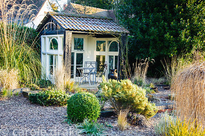Summerhouse at the top of the gravel garden is framed by grasses, evergreen shrubs including box and pine and herbaceous pere...