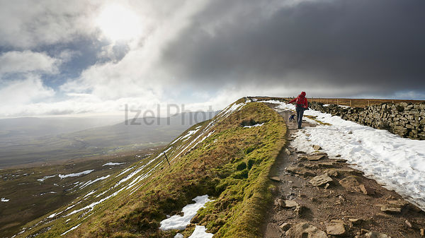 A hiker walking up to the summit of Whernside, part of the Three