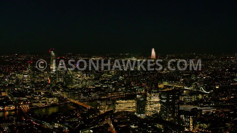 Night aerial footage of The Shard, River Thames, Tower Bridge, London.