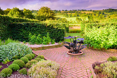 The vegetable garden with herringbone brick paths between raised beds of herbs and ironwork water feature at the Yeo Valley O...