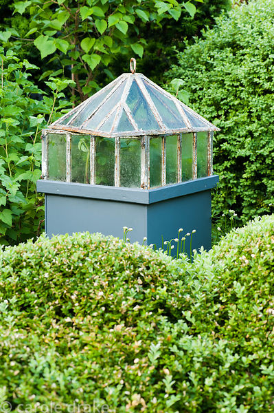 Cast iron Victorian lantern cloche set on a pedestal in the kitchen garden surrounded by fruit bushes and clipped box. Tony R...