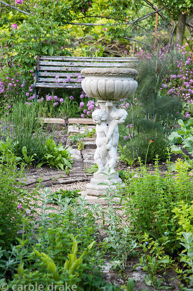 Brick path leads into the herb garden with bird bath at its centre, surrounded by marjoram, fennel and pink flowered Phuopsis...