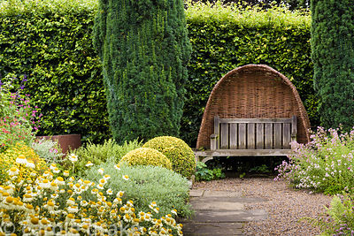 Clipped golden box, fastigiate yew and herbs frame a bench with woven willow hood in the garden at York Gate, Adel in July