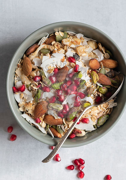 Closeup view of a healthy breakfast bowl filled with muesli, dried coconut, nuts, and pomegranate seeds.